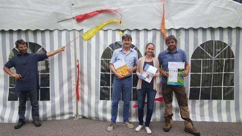 Pius Brand, Daniel Schnyder, Carmina Loosli und Rolf Schneebeli vor dem Festzelt mit Jubiläumsbroschüre und Jahresbericht. Beide Dokumente sind frisch aus der Druckerei.